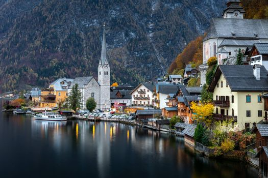 Hallsttt, Switzerland - November 2, 2019: Scenery of famous old village, world heritage Hallstatt, Austria. Hallstatt lake reflect town as mirror on water surface with dark background of mountain in early morning.