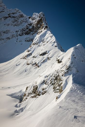 Mountain ridge covered by snow with blue sky in background, Jungfrau, Interlaken, Switzerland.