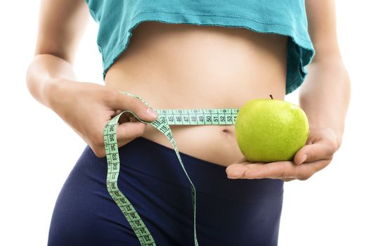 Portrait of woman in sportswear measuring her slim waist and body with a measuring tape and holding a fresh green apple, isolated on white background. Health care, dieting, weight loss or beauty concept.