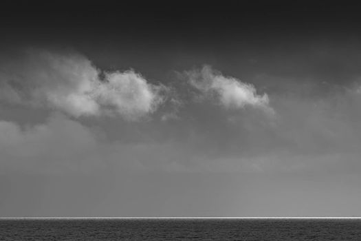White clouds over the Wadden Sea with a stripe of white light on the horizon in black and white