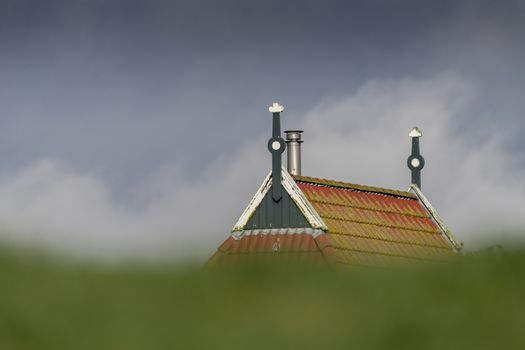 Colorful gable of a farm behind a green dike in northern Netherlands