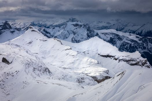 Mountains around top of Shilthorn, Switzerland covered by snow with overcast sky in winter.