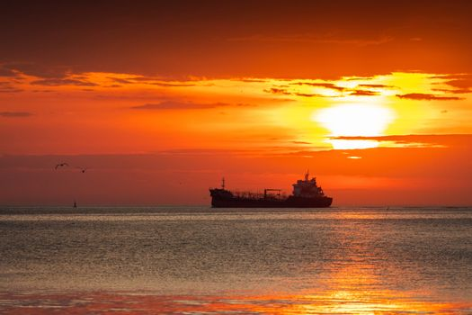 Silhouetted scene of ship and flying seagulls with cloudy orange sky at sunrise.