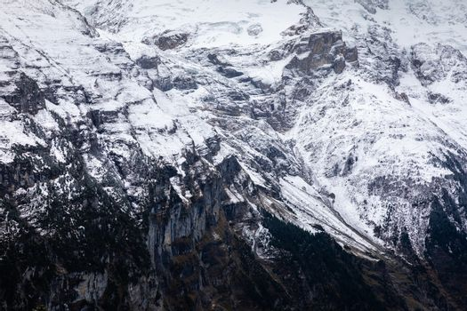 Aerial view looking from Shilthorn to black rock cliff of mountain in Jungfrau, Switzerland covered by snow on surface in winter.
