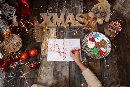 Writing a Christmas list among Christmas decorations and gingerb