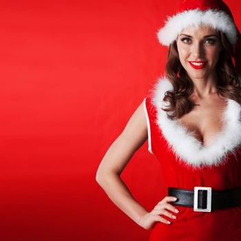 Beautiful woman in Santa Claus clothes on red background with copy space