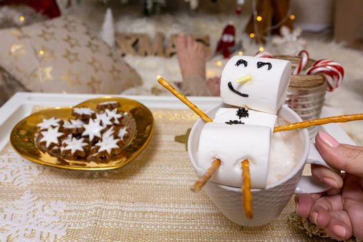 Merry snowman of marshmallow floats on a hot chocolate at Christ
