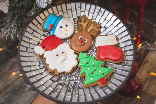 Iced gingerbread cookies by the Christmas tree