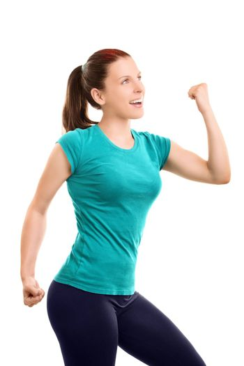 A portrait of a beautiful happy sporty fit young girl flexing her arm and cheering, isolated on white background. Healthy lifestyle concept. Freedom, happiness, relaxation concept.