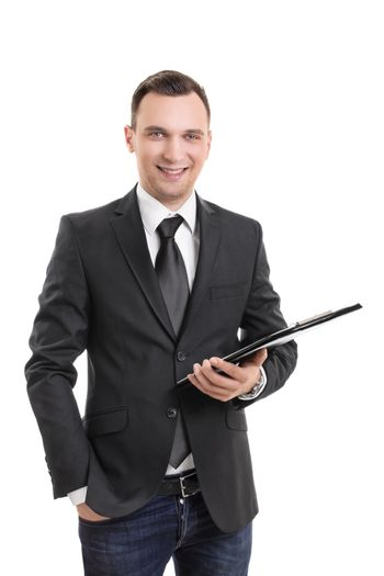 Handsome confident smiling businessman in a suit standing and holding a clipboard, isolated on white background. Young attractive businessman wearing a suit and tie, holding a notepad.