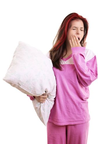 Portrait of tired young girl in pajamas holding a white pillow and yawning, with closed eyes and covering her open mouth with her palm, isolated on white background. Health balance sleep deprivation concept.