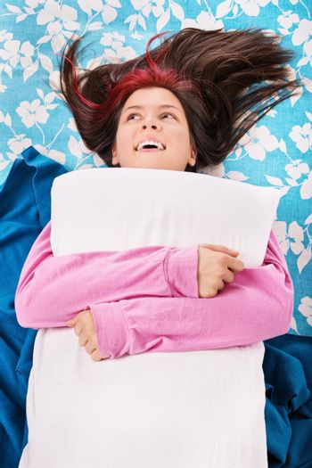 Cute young woman in pink pajamas lying in bed, smiling and hugging her pillow. Rest, sleeping, comfort and people concept. Top view.