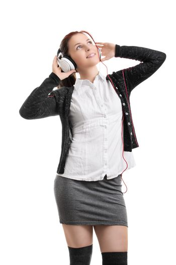 Beautiful young student girl in school uniform with headphones listening to music, isolated on white background. Portrait of a young beautiful woman enjoying music on her headphones. Music concept.