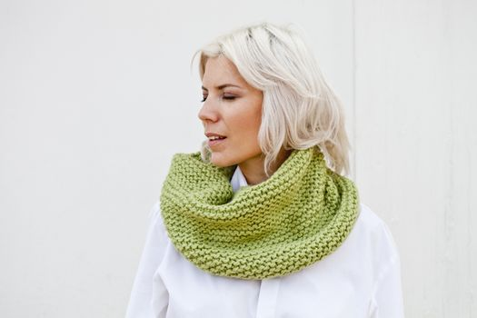 Woman in warm green wool knitted snood.