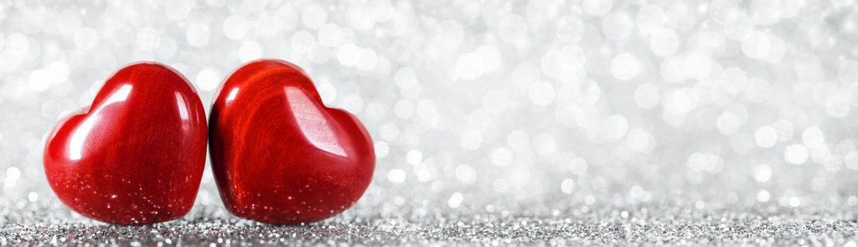 Two red wooden hearts symbol of love on background with beautiful bokeh, Saint Valentine Day celebration, copy space for text