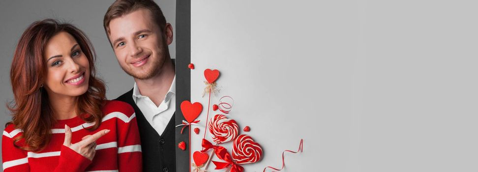 Happy young couple with heart shaped red decoration on white banner background with copy space for text. Valentine's day celebration