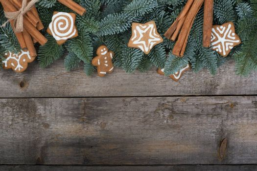 Christmas design boder frame greeting card of noble fir tree branches and gingerbread cookies on wooden background