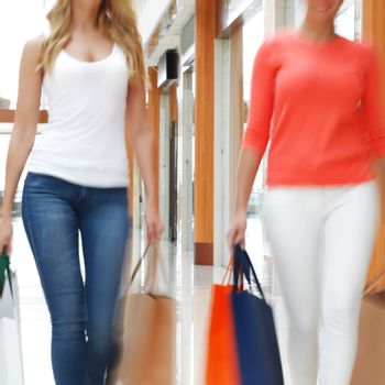 Women walking fast in shopping mall with bags sale rush concept