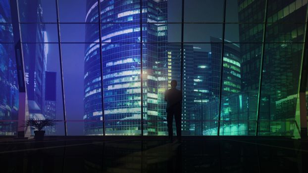 A businessman is looking at the night illumination of a business center.