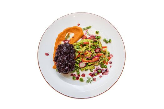Roasted beef with berries sauce garnished with vegetables, on plate isolated on white. Top view