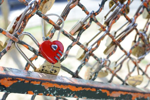 Red heart-shaped combination padlock fastened to metal fence near the Sacre Coeur basilica in Paris, France