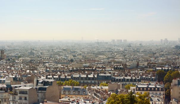 Paris cityscape seen from the steps of the Sacre Coeur basilica at Montmartre, Paris. Industrial buildings and construction beyond rows of housing and apartments.