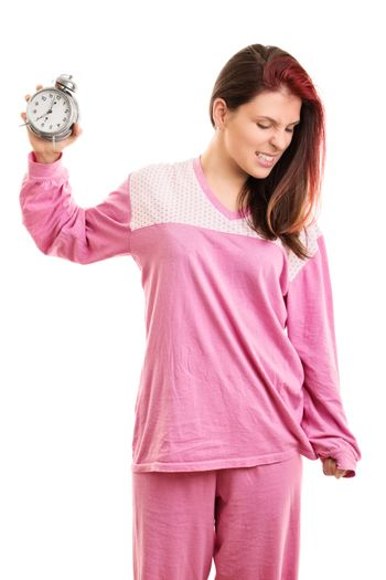 Early morning concept. Angry young woman in pink pajamas throwing a ringing alarm clock to the ground, isolated on white background. Annoyed young girl throwing alarm clock.
