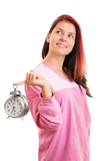 Early morning concept. Beautiful smiling young woman in pink pajamas holding an alarm clock looking up, isolated on white background.