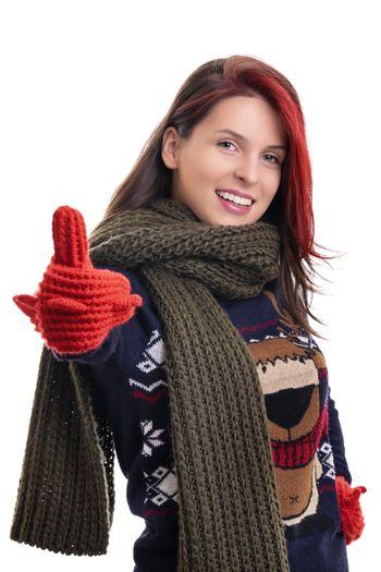 Beautiful young smiling woman in warm winter sweater, knitted scarf and mittens giving thumbs up, isolated on white background. Portrait of an attractive cheerful girl in warm winter clothes.
