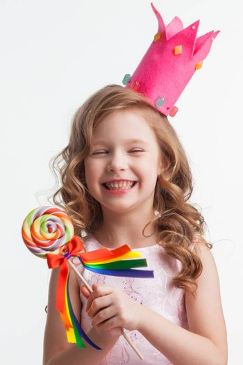 Beautiful little candy princess girl in crown holding big lollipop and laughing