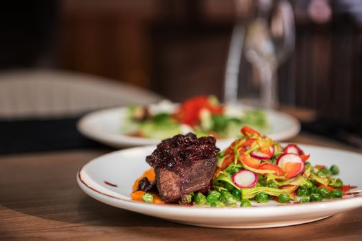 Roasted beef with berries sauce garnished with vegetables