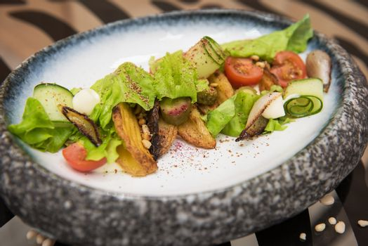 Salad with fried potato lettuce pickled cucumbers and tomatoes on decorate plate