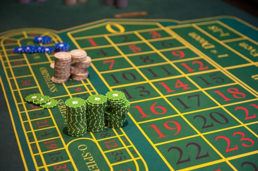 Casino, gambling and entertainment concept - green roulette table with colored chips ready to play