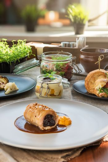 Different tasty dishes on the restaurant table, meat roll on the plate
