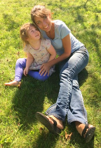Young Mother and preschool child smilimg on grass in sunlight park