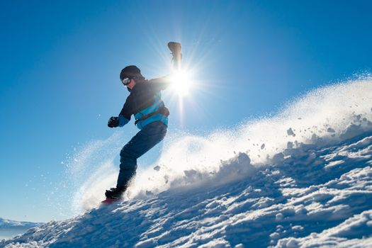Snowboarder Riding Snowboard in the Mountains at Sunny Day. Snowboarding and Winter Sports