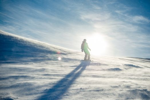 Silhouette of Snowboarder Riding Snowboard in the Mountains at Sunny Day in the Snowstorm. Snowboarding and Winter Sports