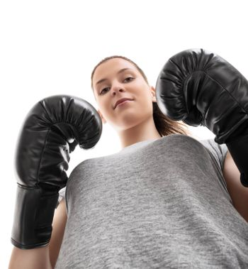 Bottom up portrait of a beautiful young woman with boxing gloves in a stance with raised arms looking down, isolated on white background.