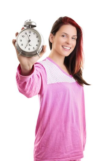Early morning concept. Beautiful young woman in pink pajamas smiling widely and holding an old fashioned alarm clock, isolated on white background.