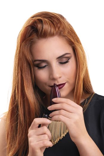 Close up of a beautiful young redheaded woman holding a perfume bottle, smelling the perfume scent with eyes closed, isolated on white background. Elegant woman enjoying the scent of her perfume.