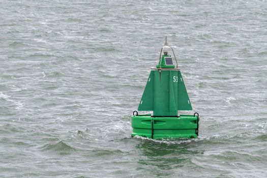 Green buoy as a marker for shipping in the Dutch Wadden Sea in the north of the Netherlands