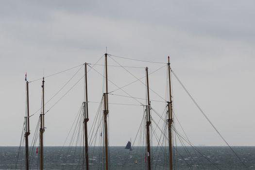 Sailboat at sea seen through the masts of two three-masted sailb