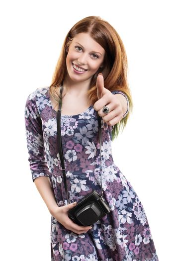 Portrait of a beautiful young girl with a vintage film camera showing thumbs up gesture with her hand, isolated on white background. Happy female photographer with a retro camera with leather case around her neck giving thumbs up.
