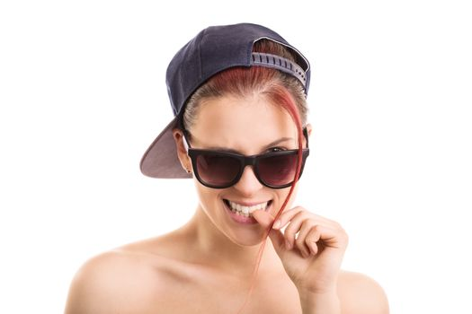 Beautiful stylish girl with backwards snapback cap and sunglasses, looking at the camera and biting her nail seductively, isolated on white background.