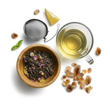 Green tea with natural aromatic additives and accessories. Top view on white background.
