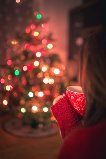 Young woman with cup of hot chocolate or tea or coffee in front of Christmas tree