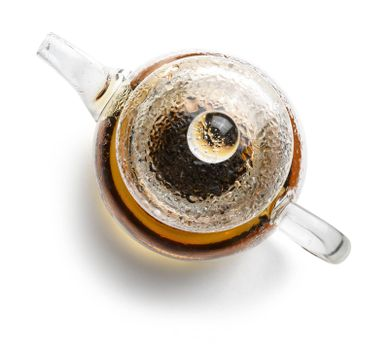 Glass teapot with tea on white background. The view from the top.