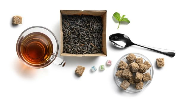 Black tea and accessories top view on white background.