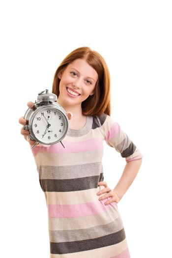 Time concept. Beautiful young girl holding an old-fashioned alarm clock and smiling, isolated on white background. Selective focus on alarm clock.