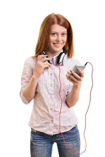 Portrait of a beautiful young girl with headphones around her neck, holding a phone and smiling, isolated on white background. Girl looking to play her favorite music.